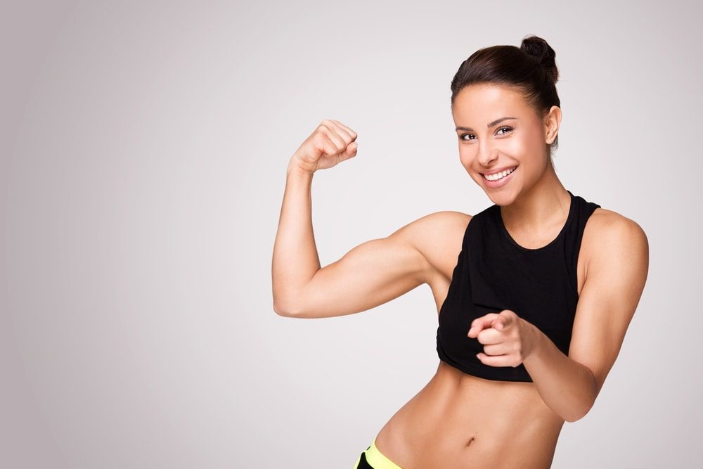 Girl showing her lean muscle with a big smile on her face